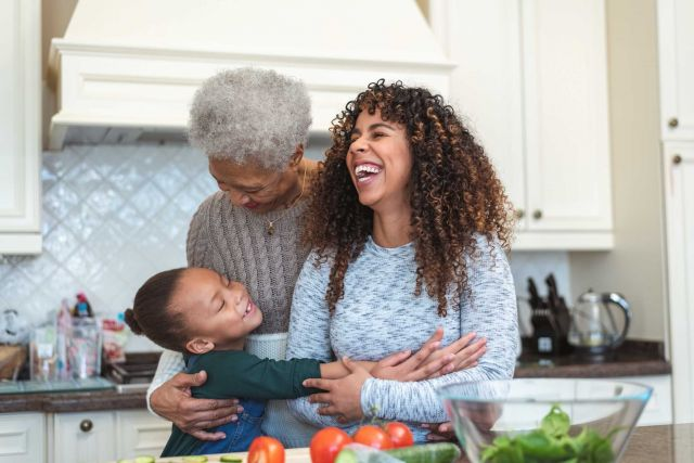 Grandmother, mother and child laughing in kitchen